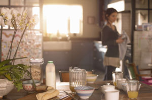 A kitchen table set for breakfast. There is morning light coming in the window and a woman in the background cleaning a glass